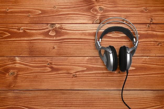 Vintage słuchawki do słuchania dźwięku i muzyki na brązowym drewnianym tle