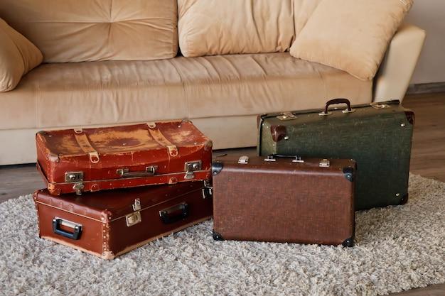 Vintage stare klasyczne przestarzałe skórzane walizki we wnętrzu jasnego pokoju przez sofę. tło z walizkami o różnych wzorach i kolorach. usiądźmy na ścieżce! koncepcja bagażu do podróży. skopiuj miejsce