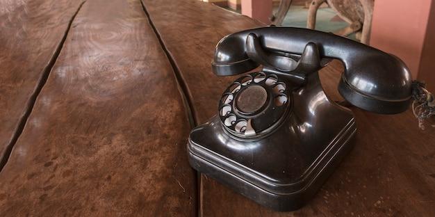 Vintage - stary czarny telefon retro na drewnianym stole