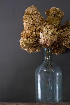 Vintage szklana butelka z bukietem suchej hortensji, naturalna ściana, selektywna ostrość