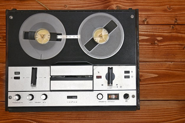 Vintage szpula do szpuli magnetofon na brązowym tle drewnianych. magnetofon retro z zsrr