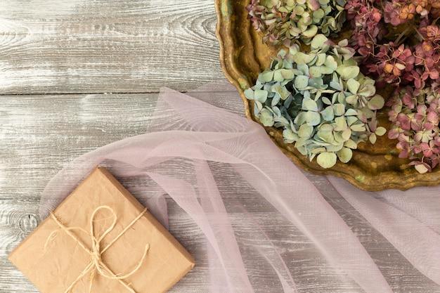 Vintage taca z suszonymi niebieskimi kwiatami hortensji, pudełko zapakowane w papier pakowy na szarym stole. płaski styl.