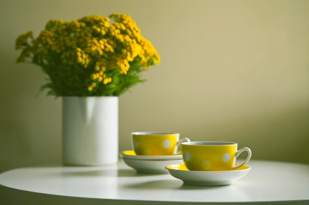 Vintage teaset - dwie żółte kropkowane kubki retro i żółte kwiaty chryzantemy na białym stole.