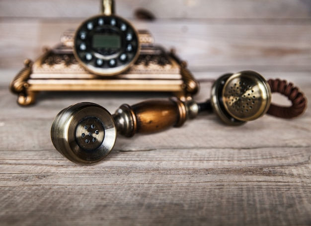 Vintage telefon na starym stole z drewna