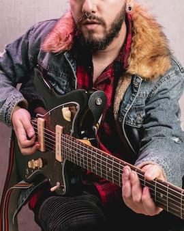 Vintage ubrany mężczyzna gra na gitarze