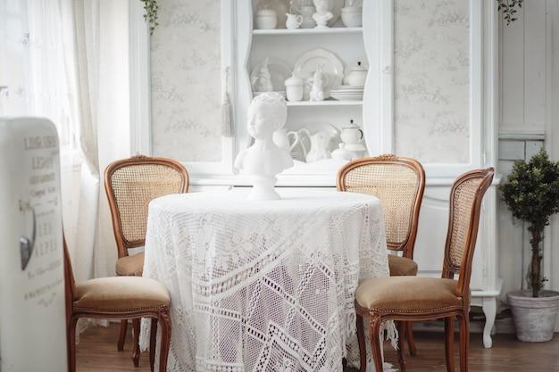 Vintage wnętrze salonu w jasnych kolorach i brązowych krzesłach