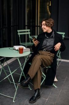 Vintage wyglądająca osoba niebinarna sprawdzająca telefon