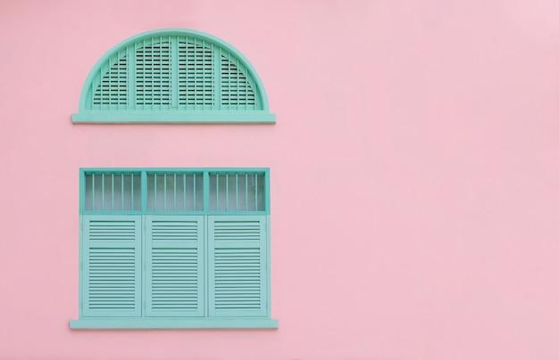 Vintage zamknięte okiennice w kolorze zielonej mięty i drewniane okna na różowo z miejscem na kopię i ścieżką przycinającą
