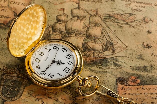 Vintage zegar kieszonkowy z białą tarczą i łańcuszkiem na tle