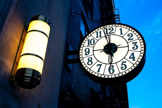 Vintage zegar uliczny na budynku w nowym jorku o zachodzie słońca