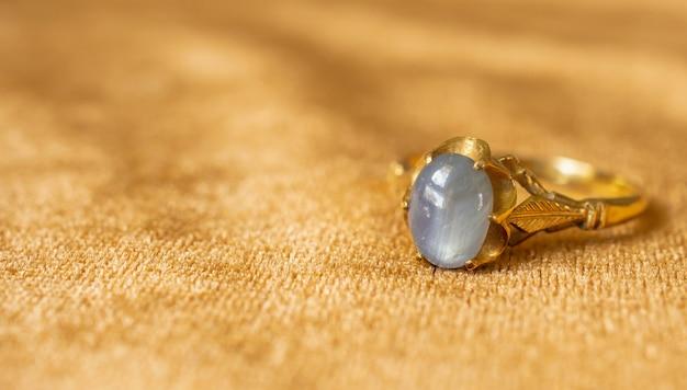 Vintage złota biżuteria pierścionek z szafirem niebieski na fakturze tkaniny