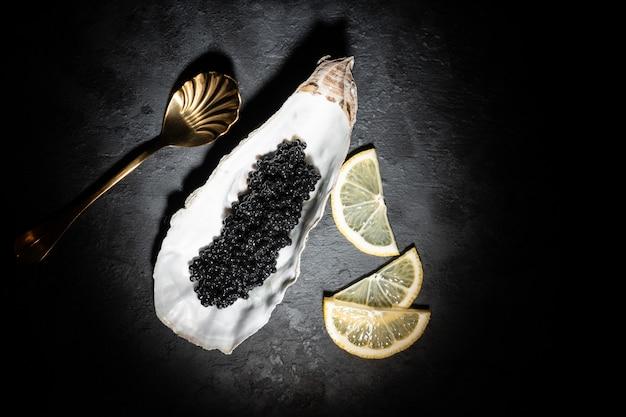 Vintage złota łyżka z czarnym kawiorem jesiotra i ostrygą na stole z czarnego kamienia łupkowego. skopiuj miejsce
