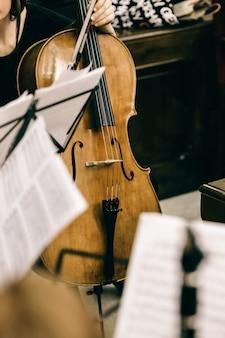 Violoncello trzymany przez muzyka podczas przerwy na koncercie muzyki klasycznej.