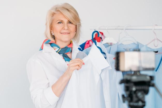 Vlog mody. uśmiechnięta kobieta w wieku. osobiste porady dotyczące stylu. nagrywanie wideo ze smartfona.