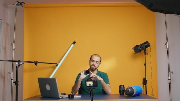 Vloger fotograficzny trzymający okrągłe filtry do aparatu podczas nagrywania wideo. przegląd filtrów nd o zmiennej gęstości optycznej, sprzęt fotograficzny i wideo sprzętu. ceator influencer, gwiazda mediów społecznościowych, rozprowadzająca online con