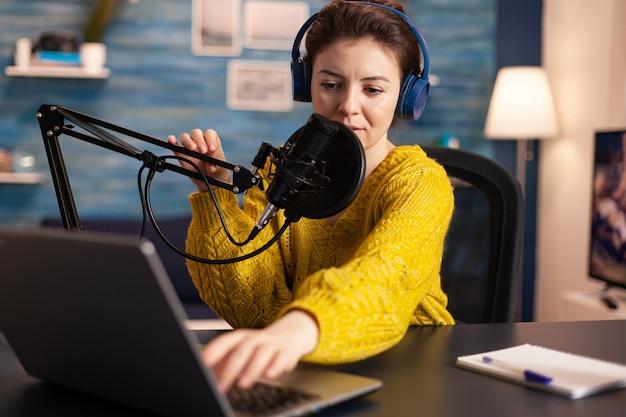 Vlogerka patrzy na laptopa i prosi widzów o zasubskrybowanie internetowego programu na jej kanale o...