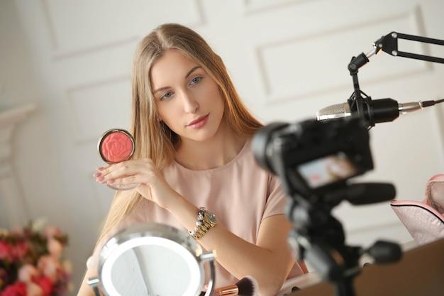 Vlogger kosmetyczny. młoda kobieta nagrywa samouczek makijażu