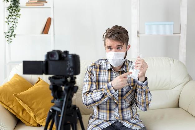 Vlogger nagrywa wideo w domu ze środkiem dezynfekującym do rąk