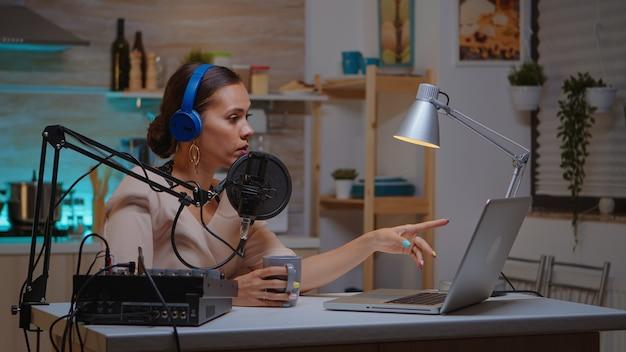 Vlogger rozmawiający na żywo z obserwatorem przy użyciu profesjonalnego mikrofonu w słuchawkach. kreatywny program online produkcja na żywo, gospodarz transmisji internetowej, przesyłający treści na żywo, nagrywający cyfrową sieć społecznościową