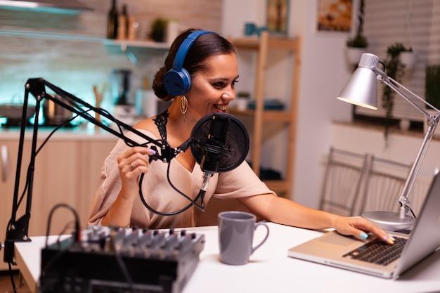 Vlogger rozmawiający na żywo z obserwatorem przy użyciu profesjonalnego mikrofonu w słuchawkach. kreatywny program online produkcja na żywo, gospodarz transmisji internetowej, transmitujący treści na żywo i nagrywanie