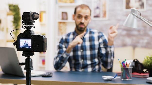 Vlogger siedzi przy biurku w salonie, rozmawiając i patrząc w kamerę. znany influencer nagrywający dla mediów społecznościowych.