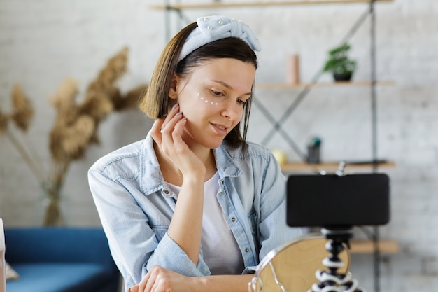 Vlogger testuje krem do twarzy i transmituje wideo na żywo do sieci społecznościowej w domu.