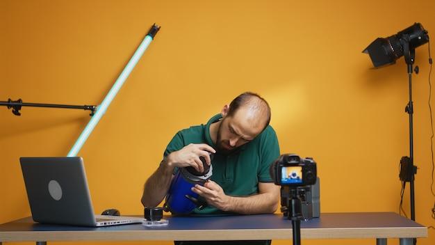 Vlogger trzymający lampkę wideo i przegląd nagrań w studio dla subskrybentów. profesjonalna technologia studyjnego sprzętu wideo i fotograficznego do pracy, gwiazda mediów społecznościowych studia fotograficznego i influencer