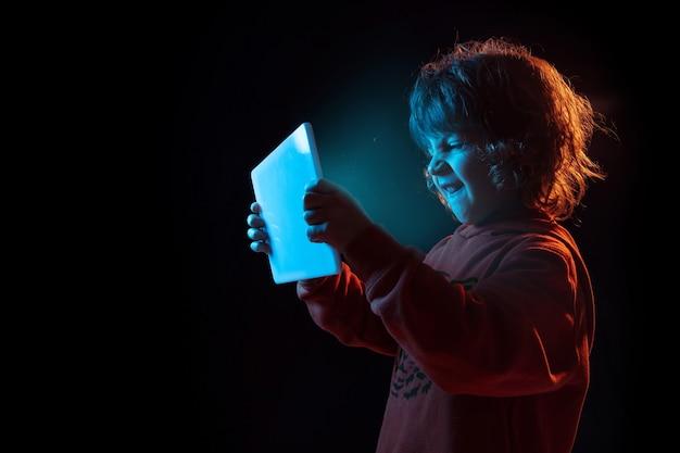 Vlogowanie z tabletem, granie. portret kaukaski chłopca na ciemnej ścianie w świetle neonu. piękny model z kręconymi włosami. pojęcie ludzkich emocji, wyraz twarzy, sprzedaż, reklama, nowoczesne technologie, gadżety.