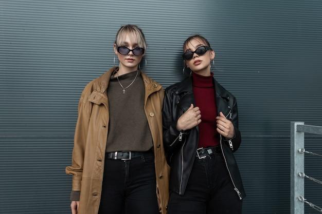 Vogue dwie modne młode kobiety w stylowych okularach przeciwsłonecznych w skórzanych kurtkach i czarnych dżinsach pozują przy metalowej ścianie na ulicy