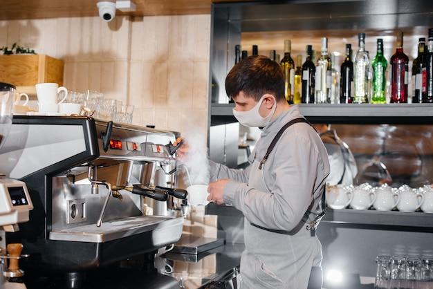 W barze kawiarni zamaskowany barista przygotowuje pyszną kawę. praca restauracji i kawiarni podczas pandemii.