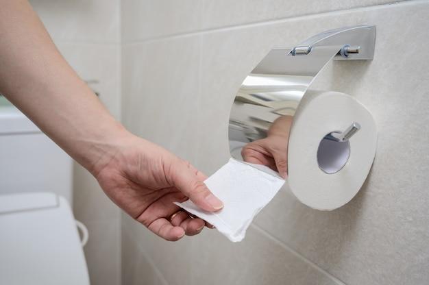 W beżowej łazience wyłożonej kafelkami ręka sięga po papier toaletowy.