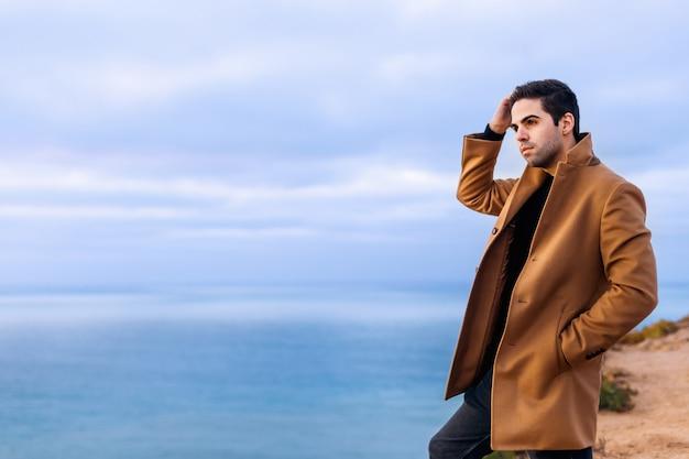 W beżowym płaszczu stojącym na brzegu oceanu i podziwiającym