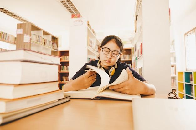 W bibliotece - studentka z młodą dziewczyną pracująca w bibliotece szkoły średniej.