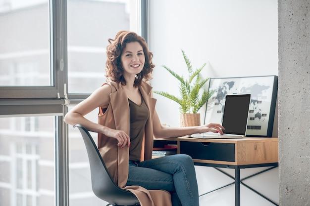 W biurze. ciemnowłosa młoda kobieta pracuje w biurze
