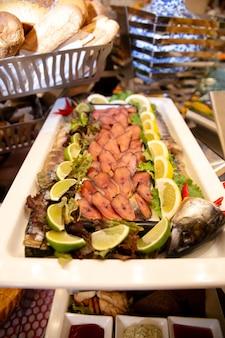 W bufecie wędzona ryba pokrojona w plasterki limonki.