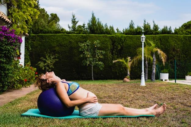 W ciąży robi ćwiczenia fitness z piłką.