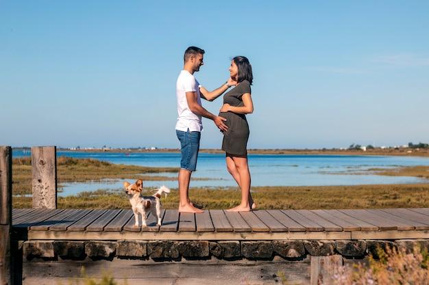 W ciąży szczęśliwa para z małym psem na plaży z małym psem na plaży na plaży na plaży