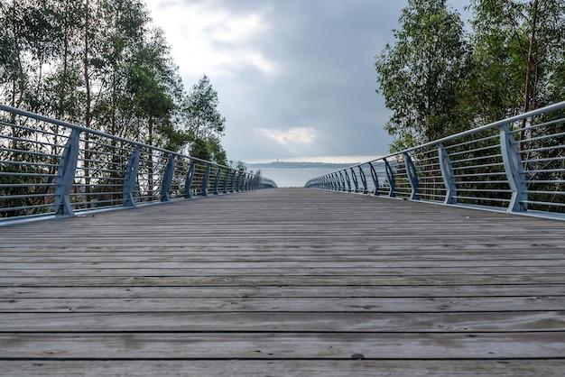 W dal prowadzi długie i szerokie drewniane przejście pod błękitnym niebem i białymi chmurami