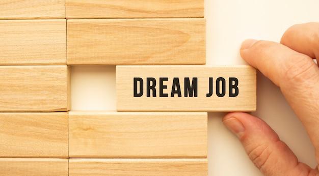 W dłoni trzyma drewnianą kostkę z napisem dream job. koncepcja pozytywnego myślenia