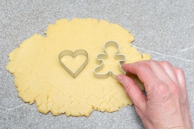 W dłoni trzyma foremkę w kształcie serca i piernik na walcowanym cieście do wypieku domowych ciasteczek.