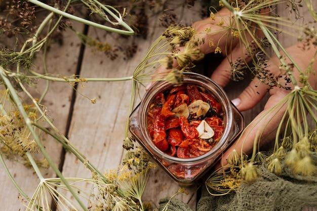 W dłoni trzyma otwarty słoik z suszonymi pomidorami z oliwą z oliwek.