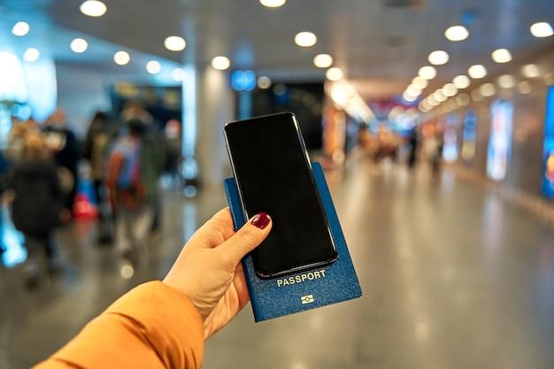 W dłoni trzyma smartfon i paszport do podróży na lotnisku