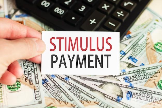 W dłoni trzyma tabliczkę z napisem stimulus payment na ścianie banknotów oraz kalkulator na stole. koncepcja finansów i ekonomii.