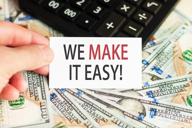 W dłoni trzyma tabliczkę z napisem - ułatwiamy to na tle banknotów i kalkulator na stole. koncepcja finansów i ekonomii.
