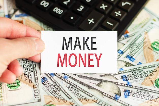 W dłoni trzyma znak z napisem - zarabiaj na tle banknotów oraz kalkulator na stole. pojęcie finansów.