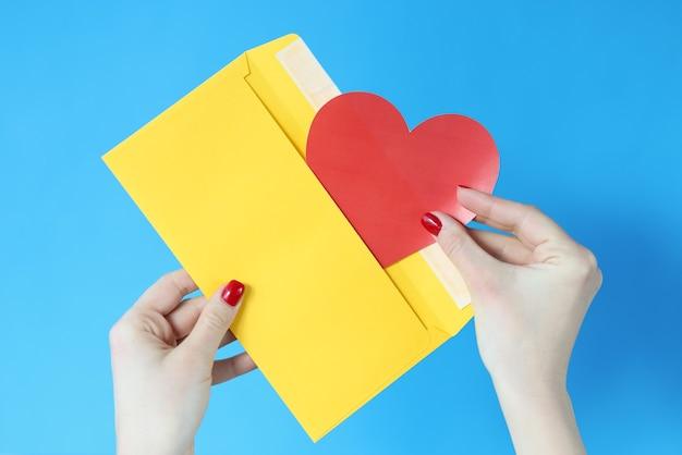 W dłoni trzyma żółtą kopertę i czerwone serce