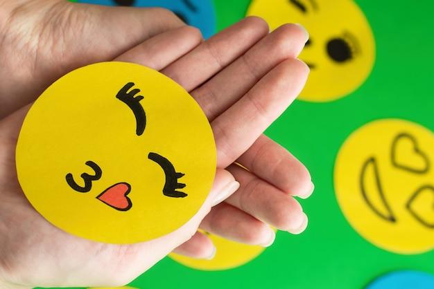 W dłoniach trzyma ikonę emotikon