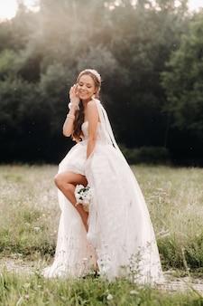 W dniu ślubu elegancka panna młoda w białej długiej sukni i rękawiczkach z bukietem w dłoniach stoi na polanie ciesząc się naturą. białoruś.