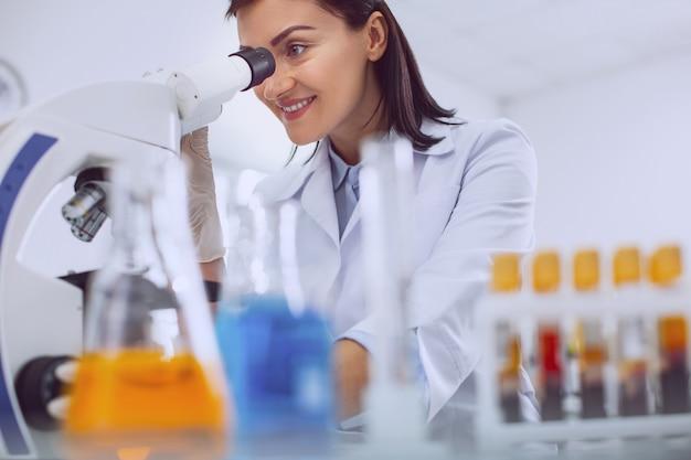 W dobrym nastroju. zawartość profesjonalnego biologa w mundurze i patrzącego w mikroskop