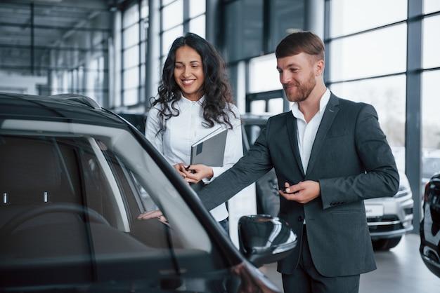 W dobrym nastroju. żeński klient i nowoczesny stylowy brodaty biznesmen w salonie samochodowym